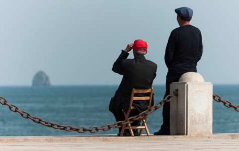 Dalian, Liaoning, China: Two elderly Chinese guys enjoying the sea at Xinghai Bay. Photo by CEphoto, Uwe Aranas 2018.