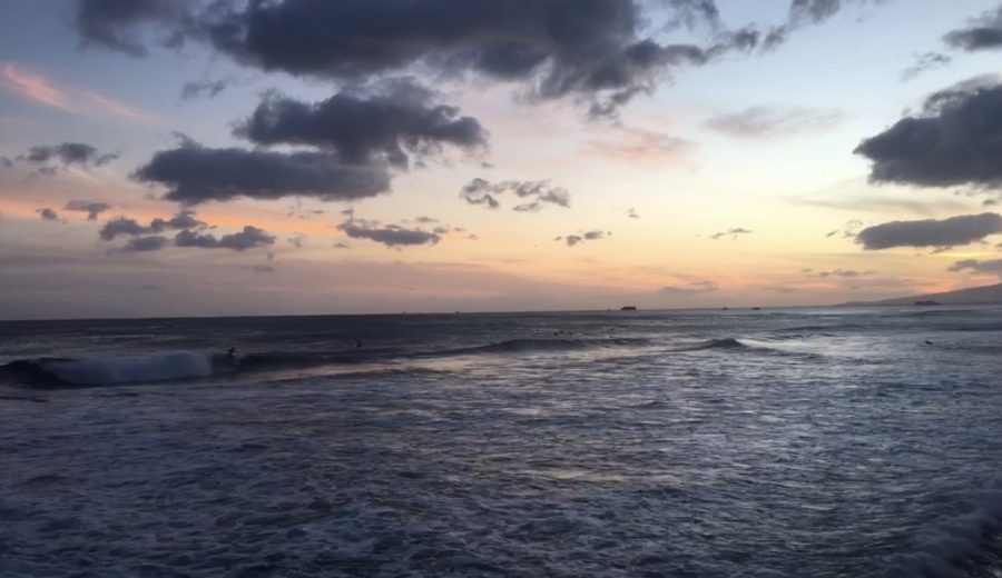 Surfers+take+off+on+a+mile-long+wave+off+Magic+Island+at+sunset.+Photo+by+Nikki+Sakumoto+2019.