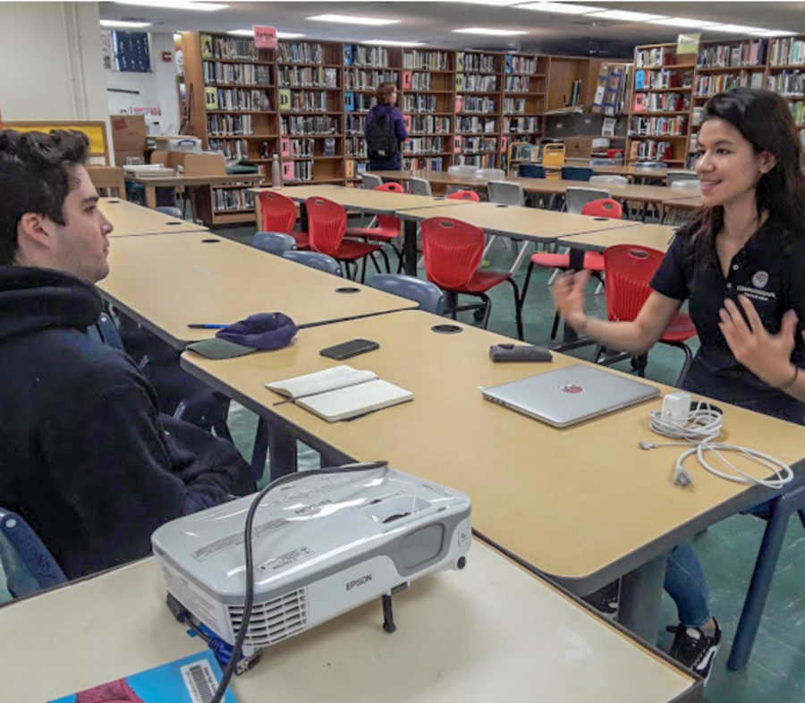 Kalani grad Tzana Saldania talks A.I. with Kalani Leo reporter Jett Neeley in the school library after giving a presentation about the future of artificial intelligence. Photo by A. Torige 2019.
