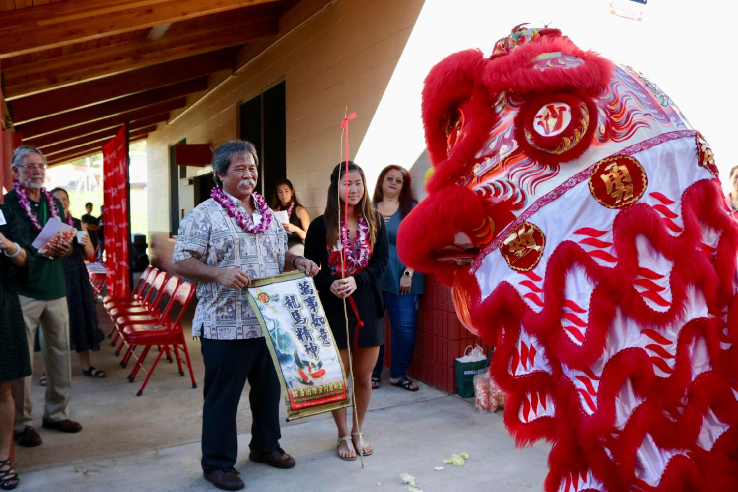 Kalani Principal Mitchell Otani stands beside Lauren Horita (12), student body president, during the lion-dance ceremony to dedicate the new girls' locker room facility on Feb. 20. Photo by S. Wong.