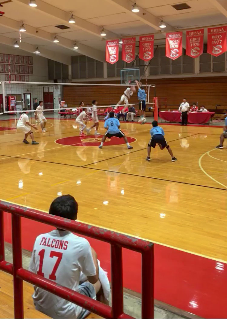 Kalani's JV volleyball team watches from the bleachers as Senior Keoni Thiim spikes a ball against Kailua in Varsity's season opener. Photo by Serena Wong 2019.