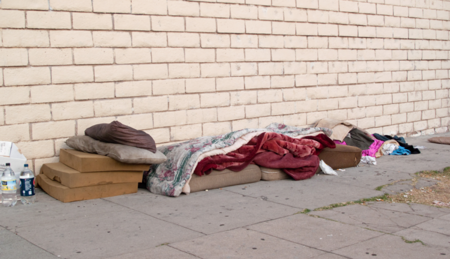 Bed, bedclothes and clothing of a homeless person who sleeps on the street. Wiki Commons 2019.