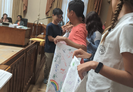 "Over 15 students from across the island showed up at Honolulu Hale on Nov.14 to support Bill 40. The students gathered hundreds of signatures from classmates to create the over 60-foot-long document they refer to as ""The Scroll"" and presented it at the hearing. Wilson Tran, a Junior at Kalani High School and head of Kalani's Green Team believes the students' efforts were successful. ""It was more than just that, and the poster exemplified this,"