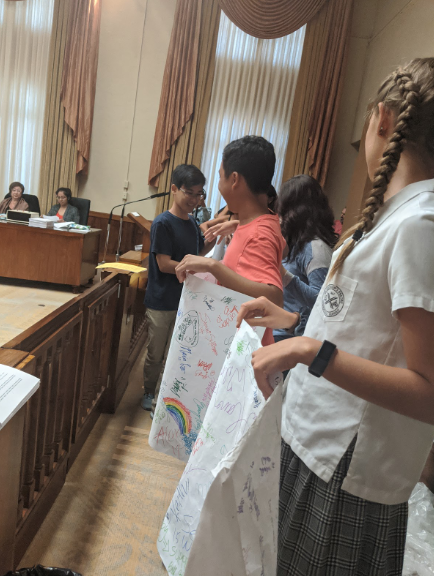 """Over 15 students from across the island showed up at Honolulu Hale on Nov.14 to support Bill 40. The students gathered hundreds of signatures from classmates to create the over 60-foot-long document they refer to as """"The Scroll"""" and presented it at the hearing. Wilson Tran, a Junior at Kalani High School and head of Kalani's Green Team believes the students efforts were successful. """"It was more than just that, and the poster exemplified this, he said. It was a showing of powerful youth support and just how much influence people can have in large numbers. It was a check on our city officials for one thing, but in the bigger picture it was saying that we want a future."""" Photo by Lucy Fagan 2019."""