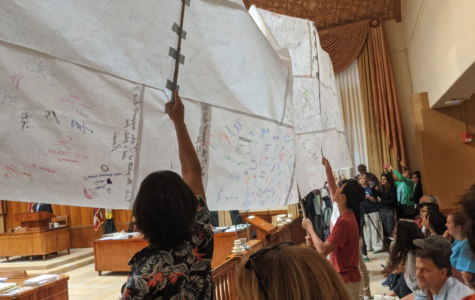 Supports of Bill 40 hold up a giant scroll featuring hundreds of signatures of support. On Wednesday, Dec. 4 Bill 40 passed the Honolulu City Council by a vote of 7-2. Photo by Lucy Fagan 2019.