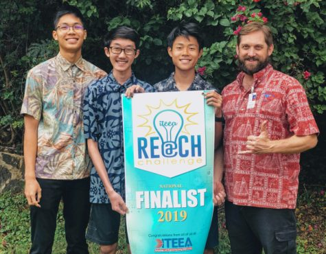 From left to right: Andy Au (10), Codie Nakamura (10),  Zi Tao Li (10), and their Robotics teacher Bryan Silver pose with their REACH Challenge Finalist banner. Photo courtesy of Zi Tao Li 2020.