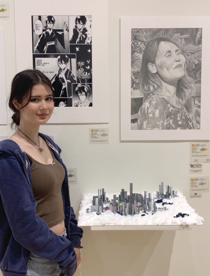 """Ai Langevin, 12, standing near her National Silver Medal art piece, """"Mother's Day"""" (top right), in the Scholastic Arts competition. Photo courtesy of Langevin. Caption by Zachary Gonsalves."""
