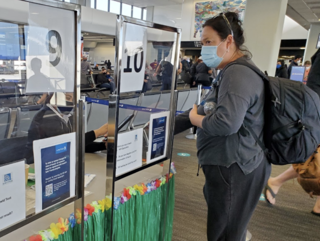 Emilani Crow shows an attendant her negative COVID-19 test result before boarding her returning flight to Hawaii from San Francisco on April 6, 2021. Travelers returning to Hawaii must have a negative test result taken within 72hours or they are required to complete a 10-day self-quarantine upon their arrival. Photo and caption by Lily Washburn.