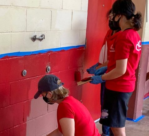 Kaydee Leong (right) and Olivia Kulaga (left) repaint one of the C-buildings walls for the Key Club campus beautification volunteer event. Photo by Ms.Takayesu.