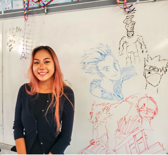 Ms. Pang poses next to whiteboard drawings of anime characters done by her students. Pang, whose favorite anime are Attack on Titan and Demon Slayer, loves sharing this interest with her students and letting them express themselves through their art. Photo by Lily Washburn.
