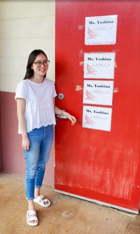 Miss Yoshina stands beside her classroom door, which displays all of her academic degrees. Photo by Ranson Silva.