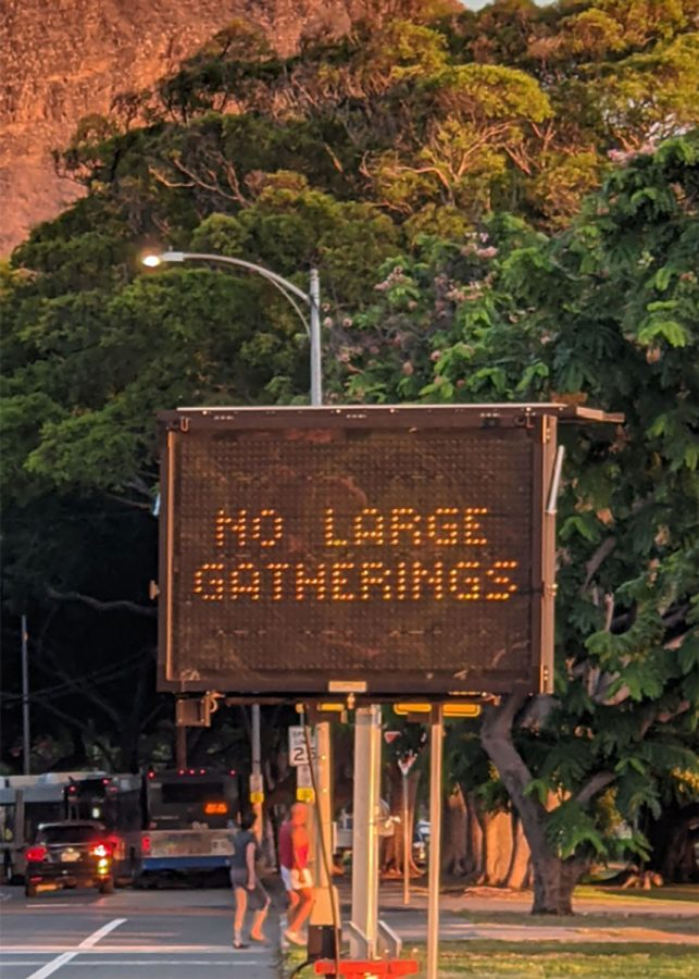 """An electronic road sign spreads the message of Covid-19, cautioning """"No large gatherings""""  at the intersection of Kalakaua and Monsarrat Avenues. The sign reminds people not to have large gatherings. It alternates through three other messages: """"Stop the spread,"""" """"Do your part,"""" and """"Violators will be cited."""" During the Covid-19 pandemic, social gatherings on Oahu have been limited to 10 people indoors and 25 people outdoors. According to KHON 2, Honolulu Mayor Rick Blangiardi extended the suspension of large gatherings. The suspension started on Sept. 22, but Blangiardi extended it until Oct. 19. To stay safe, and prevent the risk of case spikes, remember to avoid large gatherings. Photo by Eleni Cheng 2021."""