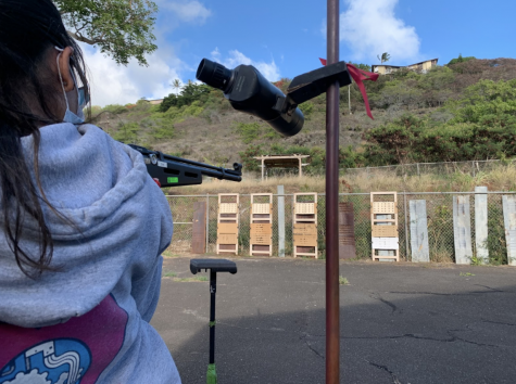 Abigayle Vendiola (11) lines up her shot for the standing position. The range -- an old, open-top parking lot shared with a shop class and the Kalani branch of Future Farmers of America -- lies adjacent to J4 and has capacity for 20 shooters. Photo and caption by Virgil Lin.